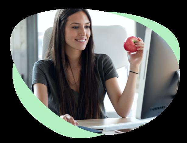 Mujer joven con manzana delante del ordenador